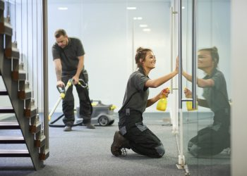 a female cleaning contractor is polishing the glass partition offices whilst In the background a male colleague steam cleans an office carpet in a empty office in between tenants.  .The female is smiling .